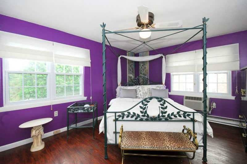 This master bedroom is surrounded by purple walls. It has hardwood flooring and a white regular ceiling.