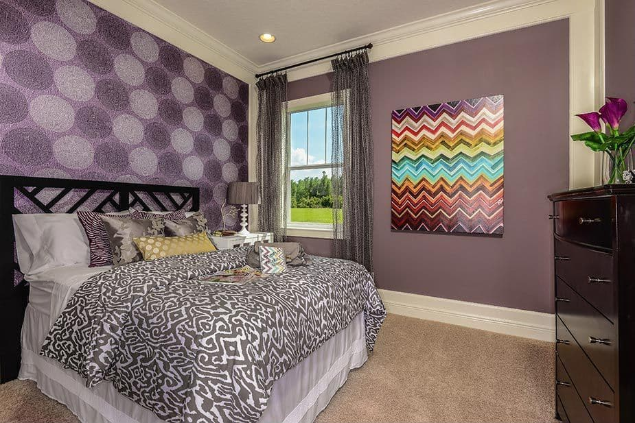 A master bedroom with carpet flooring and purple walls. The purple wall decor looks absolutely stunning as well.