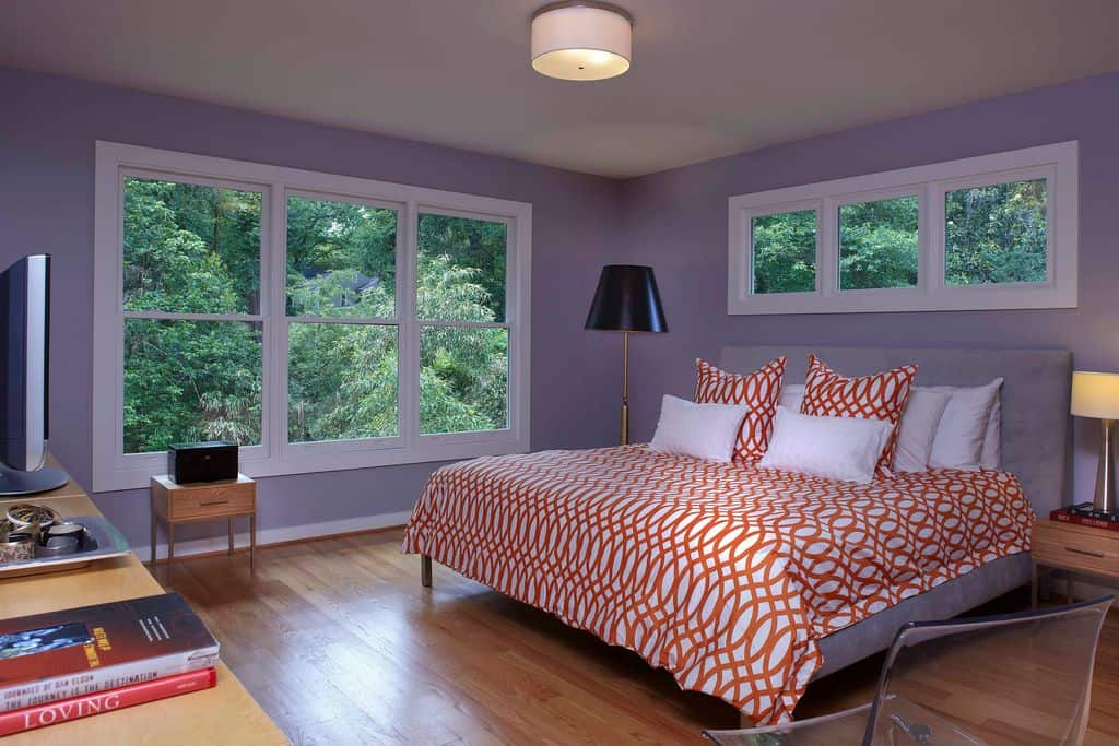Purple master bedroom with large windows and hardwood flooring. The bed has a gray bed frame with orange accent.