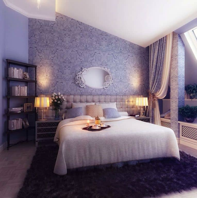 Purple master bedroom featuring a thick purple rug and a beautiful wall design. The cozy bed is lighted by two table lamps on both sides.