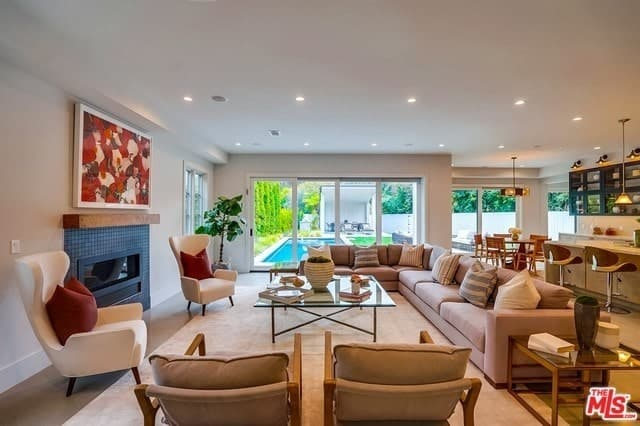 Open-concept Transitional-style living room with a fireplace and glass sliding doors.