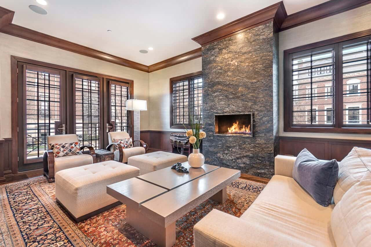 Transitional-style living room with large windows, custom millwork, a fireplace and a large area rug on wide plank flooring.