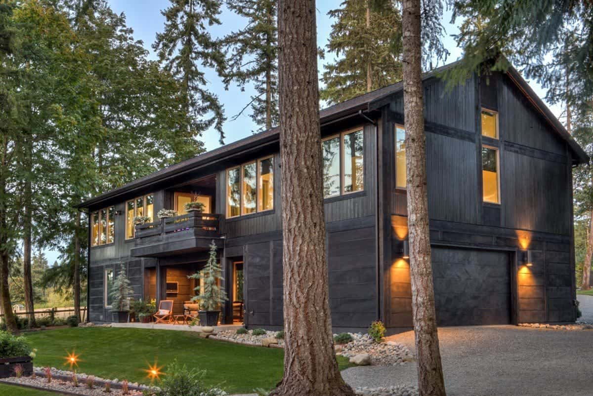 Outside view of the house showcasing its black exterior surrounded by the tall trees around the home.