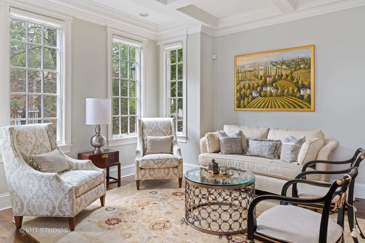 Transitional-style living room with coffered ceiling, windows, and area rug over hardwood flooring.