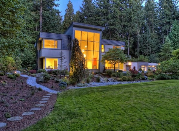 This night time view of the house showcases the large windows that has a warm and welcoming glow. These are wonderfully framed by the lush green landscaping that is filled with a grass lawn, various shrubs and tall pine trees in the background.