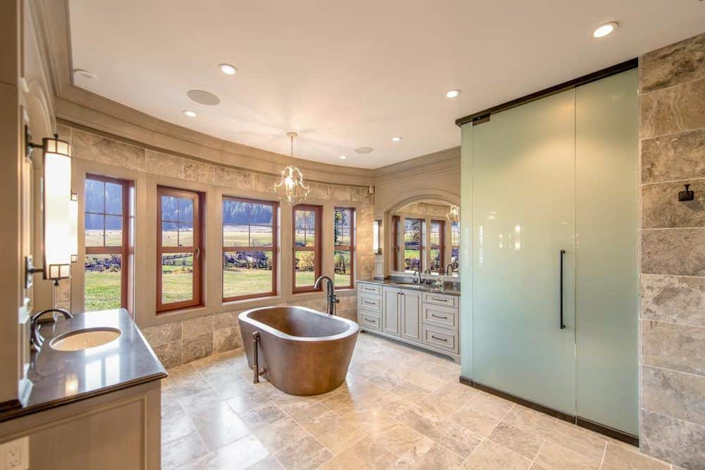 This bathroom has an earthy brown stone freestanding bathtub in the middle of the beige marble flooring. It has a row of windows on one side and the two vanities on either side of the wall. There is also a shower area enclosed with frosted glass for privacy.