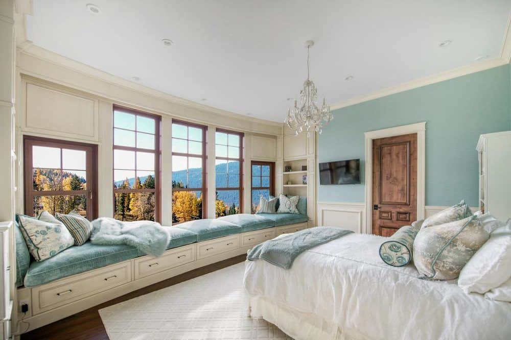 This other bedroom has a long cushioned built-in bench across from the bed. This is placed under the row of windows for a comfortable reading nook with lovely pastel-colored cushions to match the walls above the wainscoting.