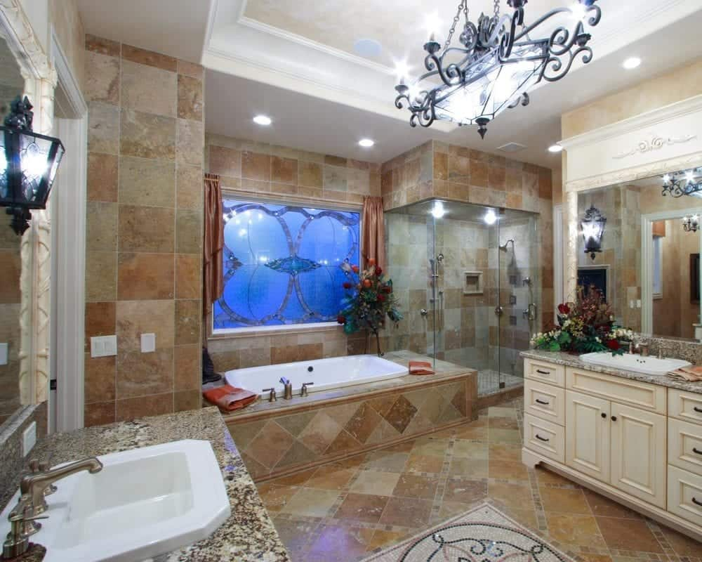 This is the primary bathroom that has a wrought iron chandelier above the earthy tiles of the flooring. These tiles are also used to house the bathtub in the corner beside the glass-enclosed shower area.