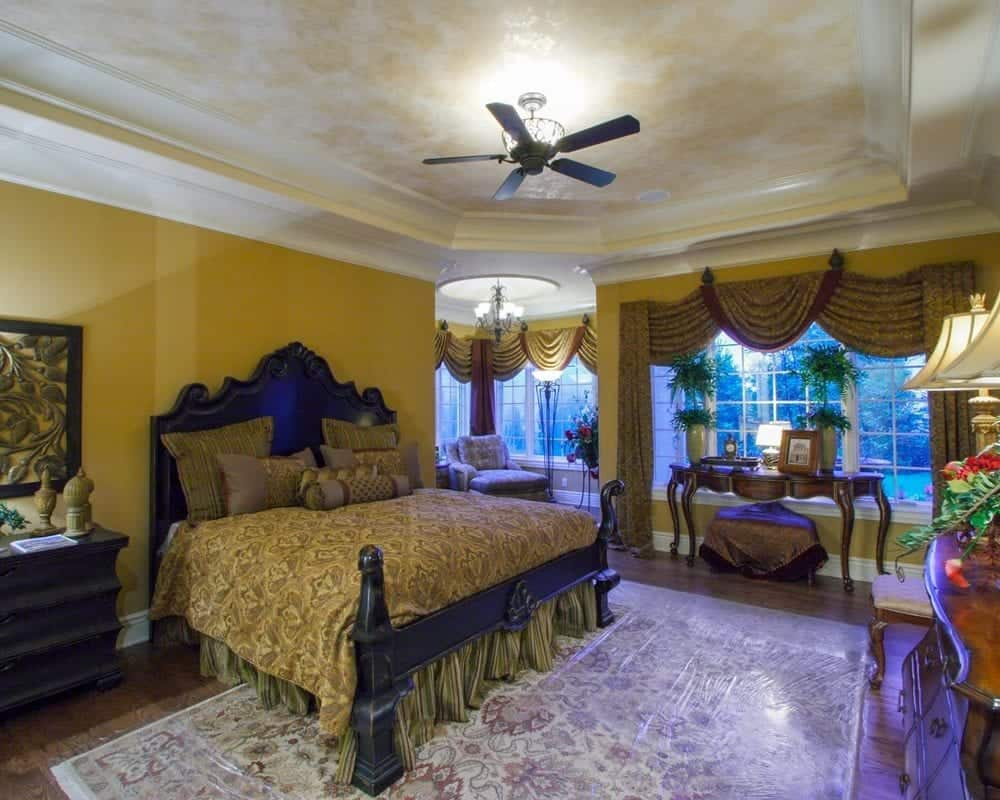 This is the primary bedroom with a large wooden sleigh bed that stands out against the earthy beige walls and bed sheets. This matches with the console table on the far side placed by the wide window that has curtains of the same tone as the bed sheet.