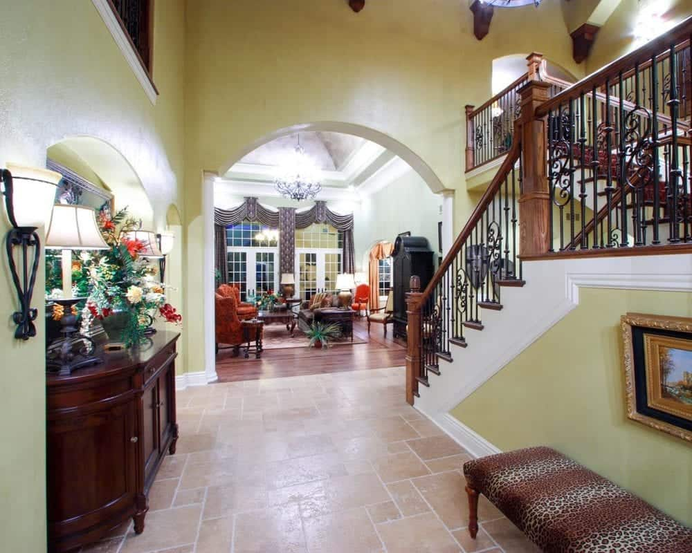 This is the foyer of the house with a tall ceiling that contrasts with the surrounding beige walls and has a cushioned bench on the side for waiting guests.