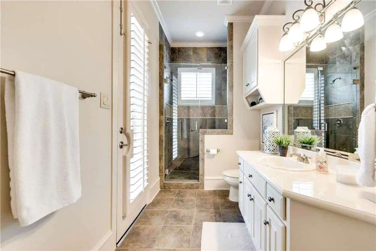 This charming bathroom has earthy brown marble flooring tiles to complement the beige tones of the walls and vanity. On the far side of this bathroom is the walk-in shower area with a glass door.