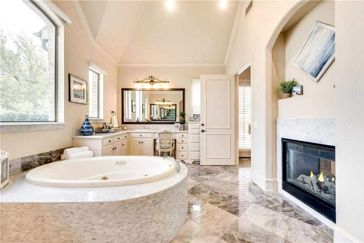 This spacious bathroom has a large circular bathtub by the large glass window warmed by a lovely fireplace embedded into the beige wall.