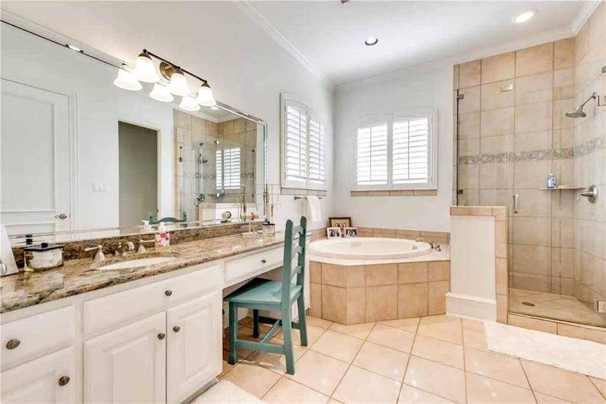 This is a charming bathroom with a corner bathtub in the middle of the beige vanity and the glass-enclosed shower area.