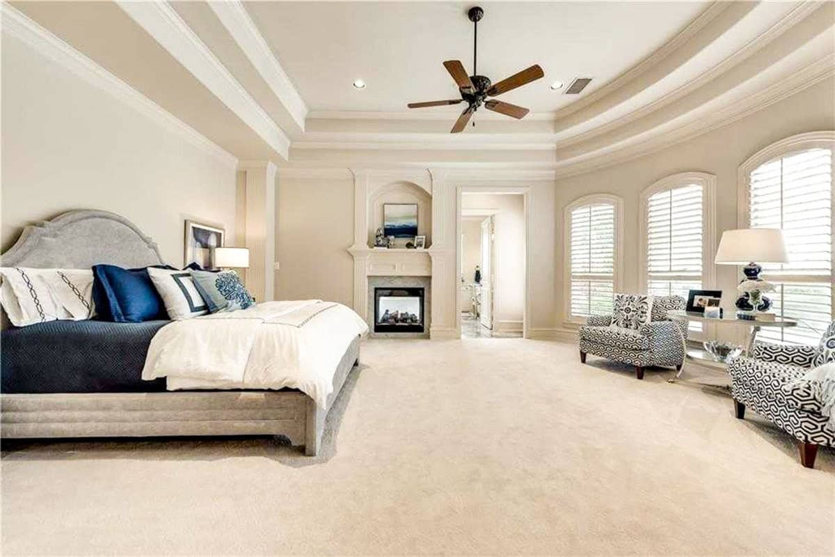 This is a spacious and bright bedroom that has a beige carpeted flooring to match the beige walls and beige tray ceiling. The large gray bed is complemented by the fireplace on the far side and the row of tall windows at the sitting area.