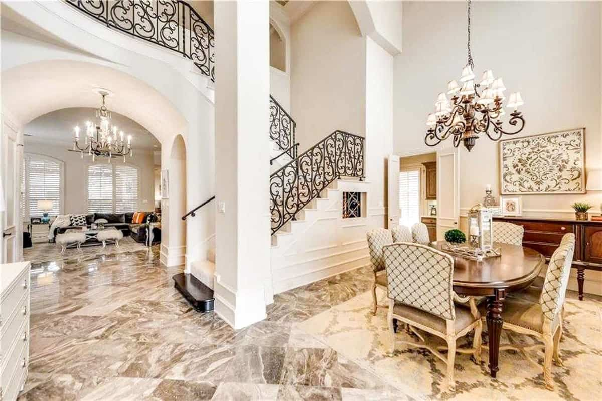 This is the formal dining room just beside the beige staircase with wrought iron railings and tall beige pillars. The dining area is topped with a charming chandelier hanging over the wooden dining table.
