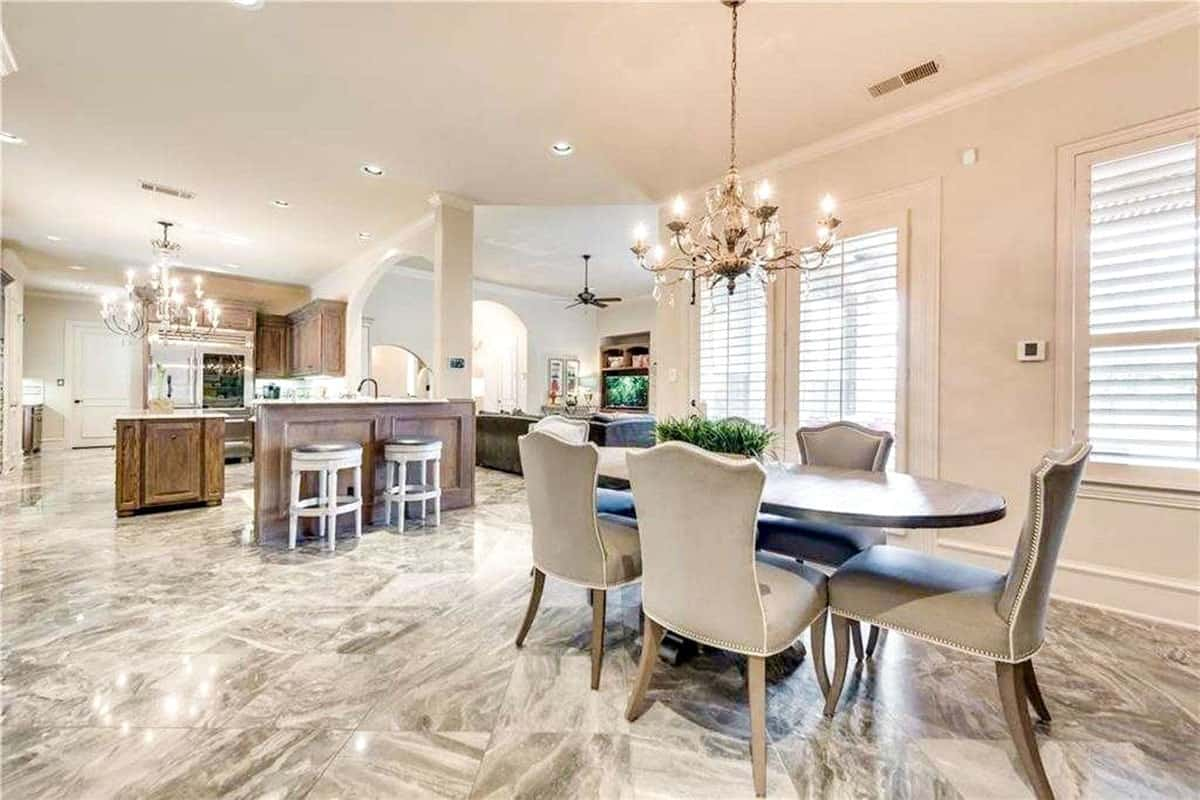 This is the informal dining area just beside the kitchen. It has a simple chandelier hanging over the elliptical dining table surrounded by cushioned chairs.