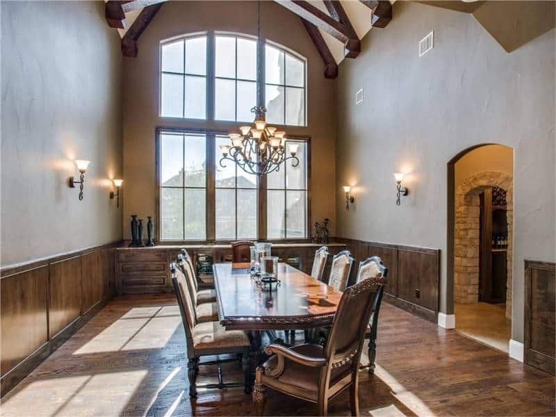 This is a grand formal dining room with a dark wooden dining set that matches well with the hardwood flooring. This also matches with the wooden wainscoting and the exposed large beams of the tall arched ceiling.