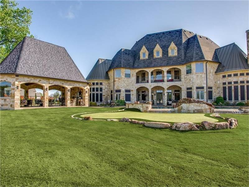 The back of the houses has a wide lawn of grass perfect for playing golf. In the middle of it is a small spot with a different shade of grass surrounded by decorative large rocks.