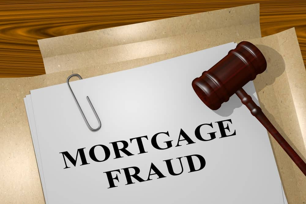 """The words """"Mortgage Fraud"""" written on a sheet with a paper clip and a gavel on top."""