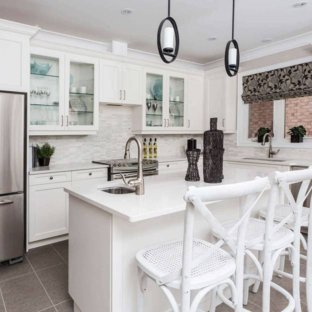 The white shaker cabinets complete the overall aesthetic of this kitchen that features simple white lines that is complemented by a gray-tiled floor.