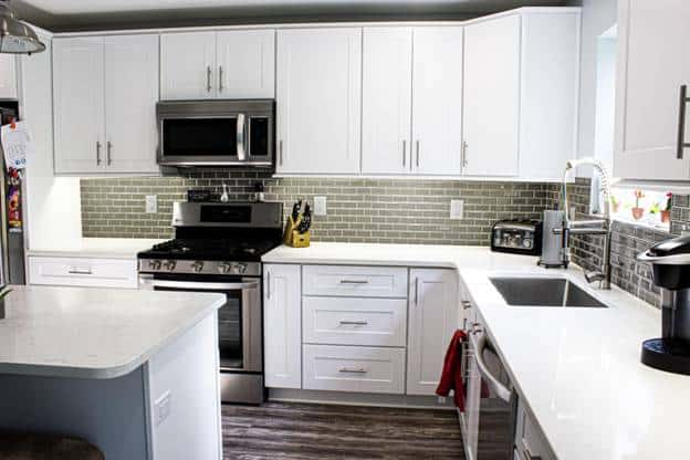 The white kitchen cabinets and drawers are a good pairing for the small gray tiles of the backsplash that is arranged in a brick wall pattern serving a nice contrast for the white countertop.