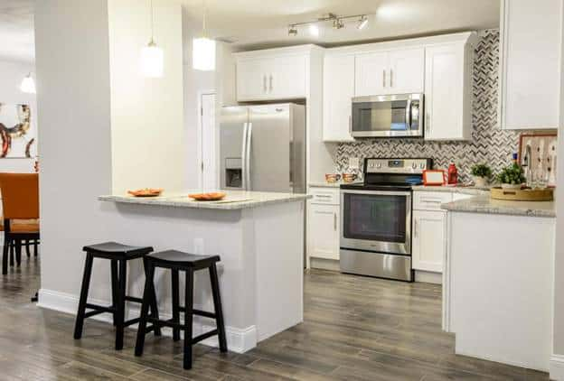 This kitchen features the contrast between the clean white shaker cabinets and the complex patterns of the gray backsplash as well as the tiled floor.