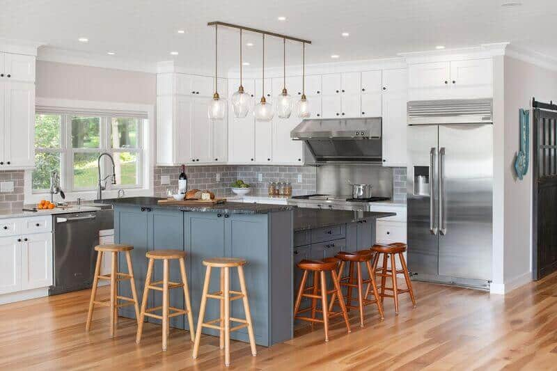 The beautiful kitchen island features shaker cabinets and drawers painted in a lovely gray matte palette that matches the black marble countertop and the wooden stools.