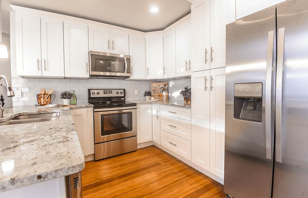 The white shaker cabinets of the hanging wooden structure follow the lay of the kitchen wall and connect with the kitchen peninsula to allow ample hardwood floor space.
