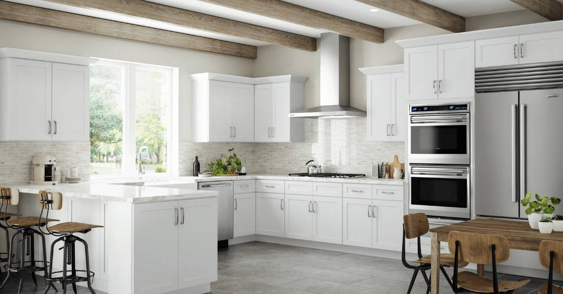 The white ceiling has exposed wooden beams that serve as a nice contrast for the white shaker cabinets and drawers of the U-shaped kitchen peninsula.