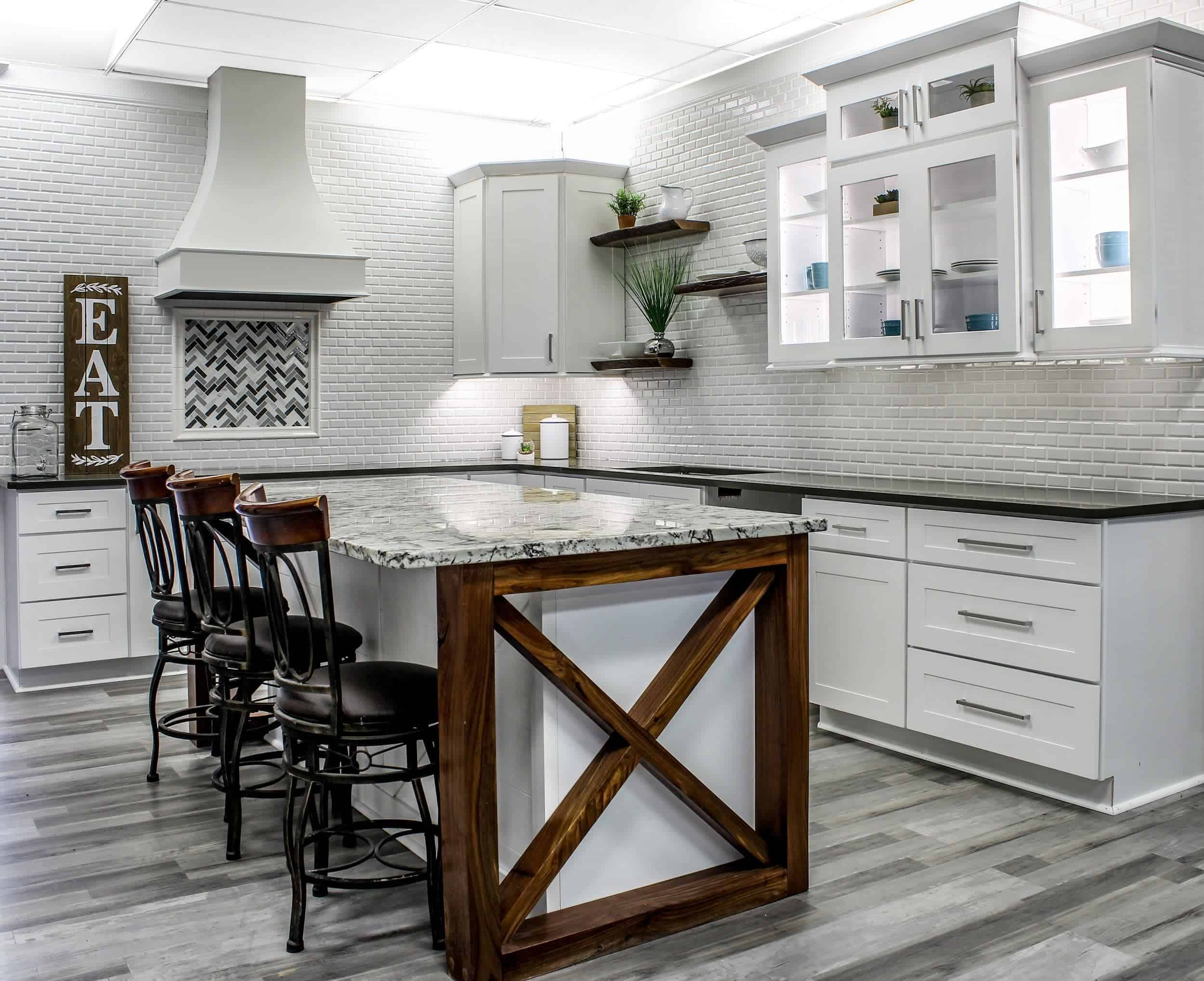This is a bright and spacious kitchen due to its white shaker cabinets that are fitted with brilliant backlights paired with white backsplash tiles arranged in a brick wall pattern.