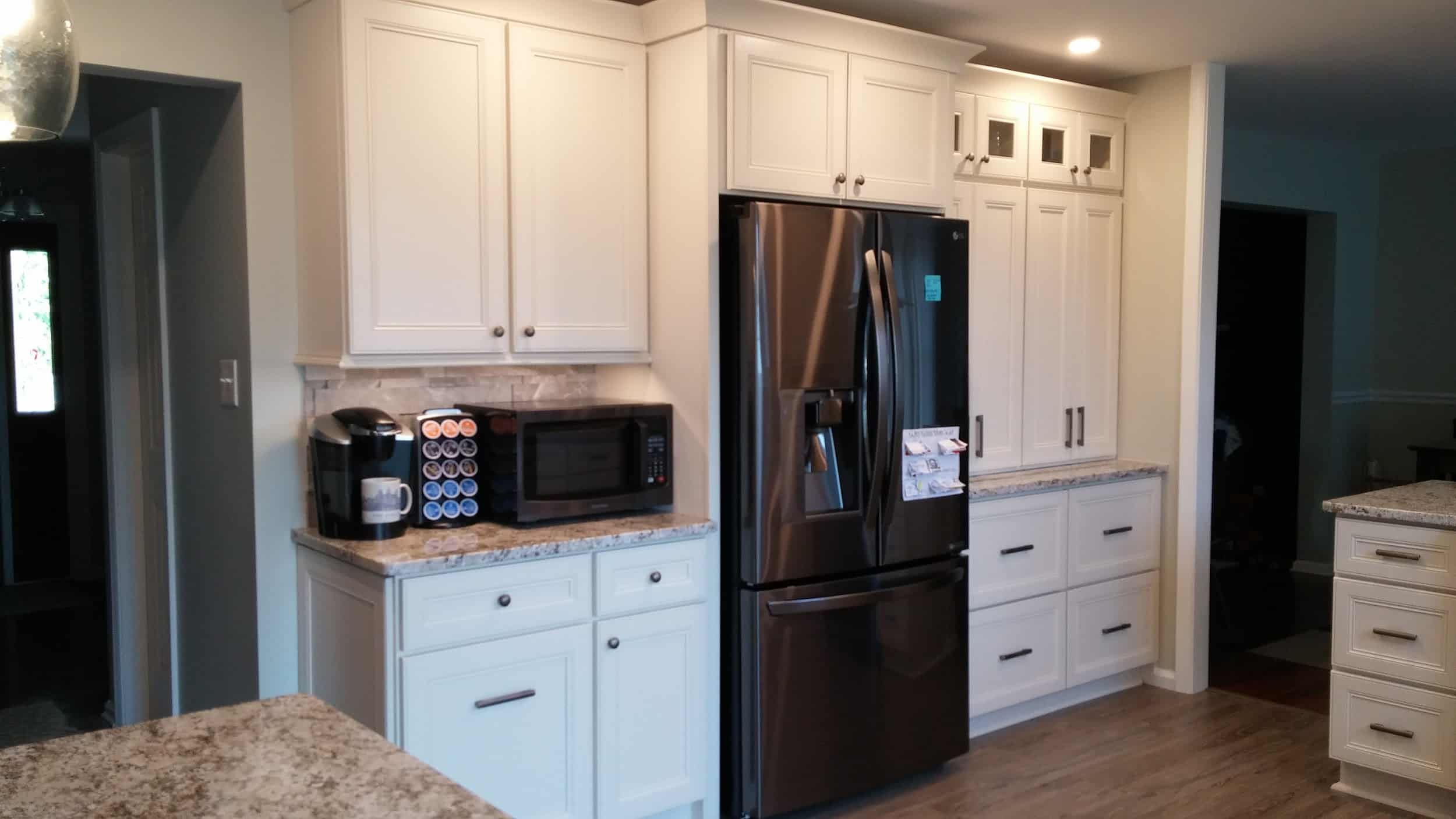The sleek modern black fridge is perfectly framed with the contrast of white shaker cabinets and drawers that have two types of handles.