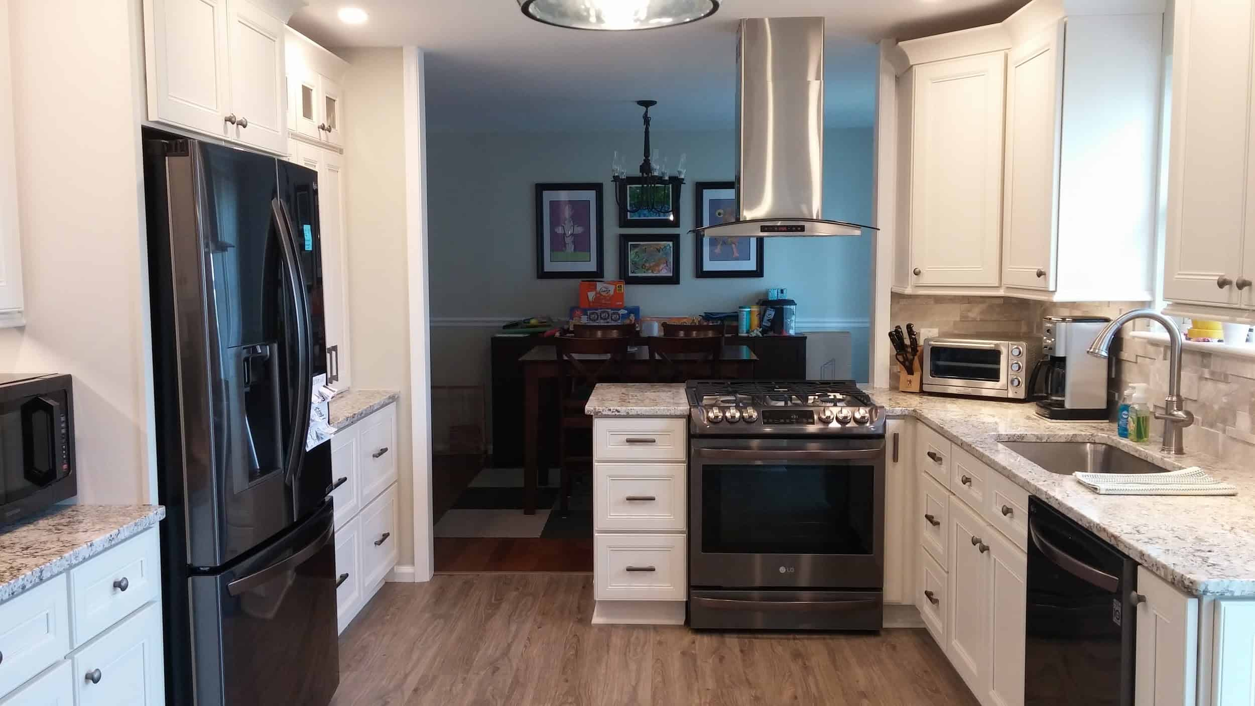 The L-shaped kitchen peninsula with white shaker cabinets and drawers houses the oven stove and dishwasher as well as the kitchen sink paired with gray marble countertops.
