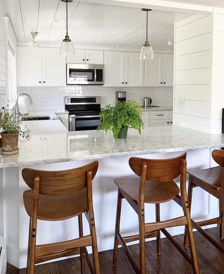 This lovely kitchen has a white theme that is consistent on the wooden shiplap ceiling, marble countertops, backsplash, and the shaker cabinets and drawers.