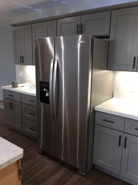 The silver modern fridge is complemented by the light gray hues of the shaker cabinets and drawers that are given black handles to complete the aesthetic.