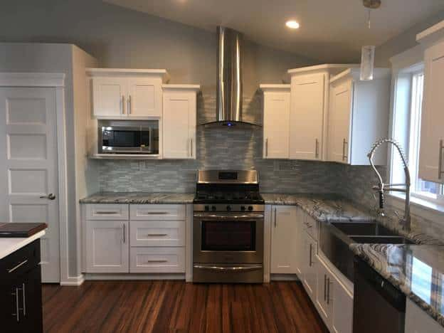 The metallic sink matches well with the modern appliances and the gray marble countertops of the L-shaped peninsula that has white shaker cabinets and drawers.