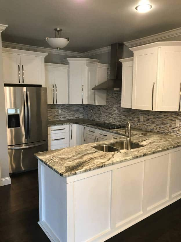 The U-shaped peninsula has gray marble countertops that match with the complex patterns of the backsplash tiles that are perfectly framed with the traditional white shaker cabinets and drawers that have stylish elongated silver handles.