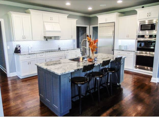 This kitchen features the shaker cabinet design on the peninsulas and hanging cabinets that are not quite touching the gray ceiling. This enables you to see the gorgeous white molding that matches those at the top of the cabinets.