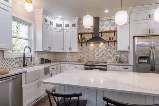 This is a nice pairing of the traditional aesthetic of the white shaker cabinets and the herringbone backsplash made of small white tiles bordered with dark grout to emphasize the pattern.