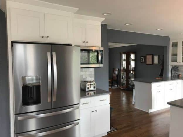 The gray elements of the fridge, walls, and the kitchen countertops are well suited for the white shaker cabinets and drawers that are contrasted by the hardwood flooring.