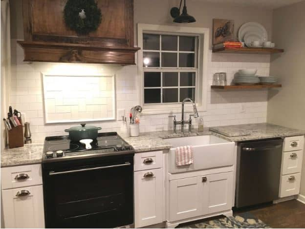 This charming kitchen features white shaker cabinets and drawers that contrast the sleek black appliances and is mediated by the gray marble countertop.