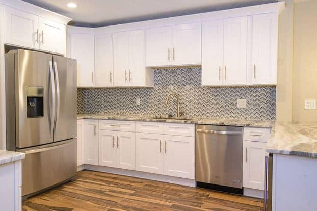 The sleek modern fridge and matching dishwasher stands out against the shaker cabinets and drawers that frames the herringbone patterns of the backsplash.
