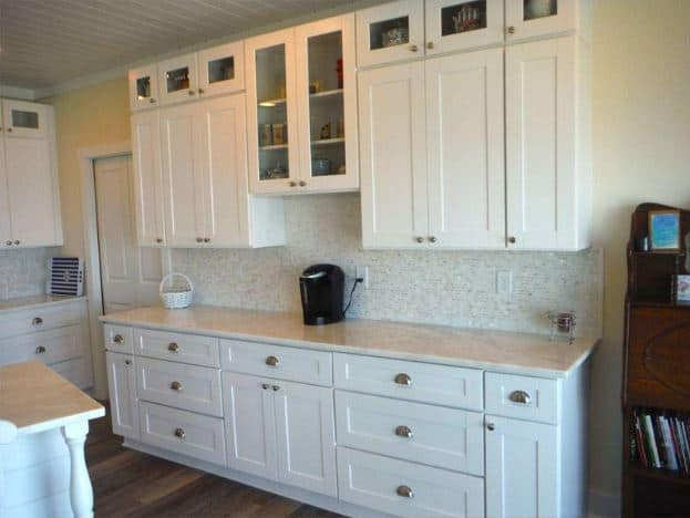 The subtle white lines of the white wooden shiplap ceiling are a perfect match for the white shaker cabinets and drawers that have modern silver handles.