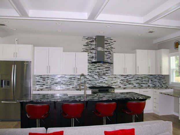 The red wingback stools along with the black kitchen island are the centerpiece of this white kitchen that has white shaker cabinets and drawers.