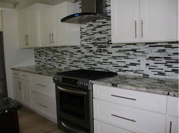 The complex patterns of the backsplash's black and white tiles stand out against the traditional white shaker cabinets and drawers that blend in with the white walls and ceiling.