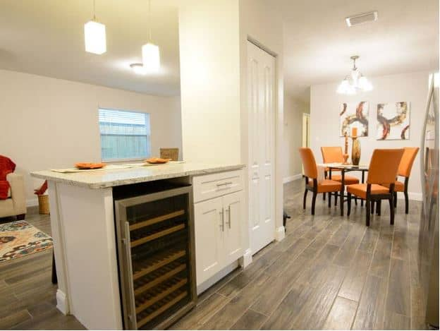 This hardwood floored kitchen features a white kitchen island with a wine fridge beside shaker cabinets that match the pantry attached to the kitchen island.
