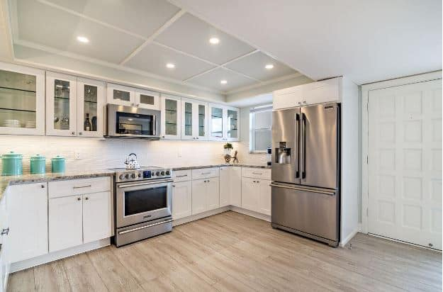 The white shaker design is applied to the white cabinets, drawers, tray ceiling, and the kitchen door. This is well contrasted by the hardwood flooring and the sleek modern kitchen appliances.