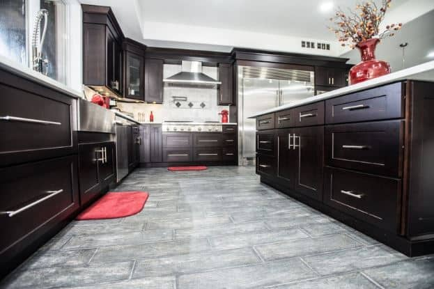 The dark wood tones of the shaker cabinets and drawers emphasize the silver handles that match perfectly with the flooring and the sleek modern appliances.
