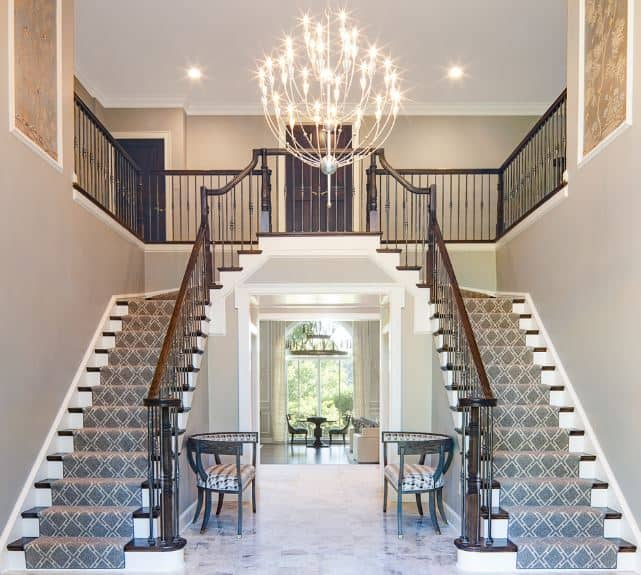 This grand Transitional-Style foyer's highlight is the brilliant chandelier hanging from the high white ceiling that looks like a dandelion. This illuminated the gray walls and gray patterned carpeting of the dual stairs.