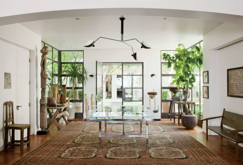 This is a large foyer with hardwood flooring dominated by a large red patterned area rug and on its sides are wooden decors, chairs and tables as well as potted plants that is contrasted by the modern lights of the white ceiling.