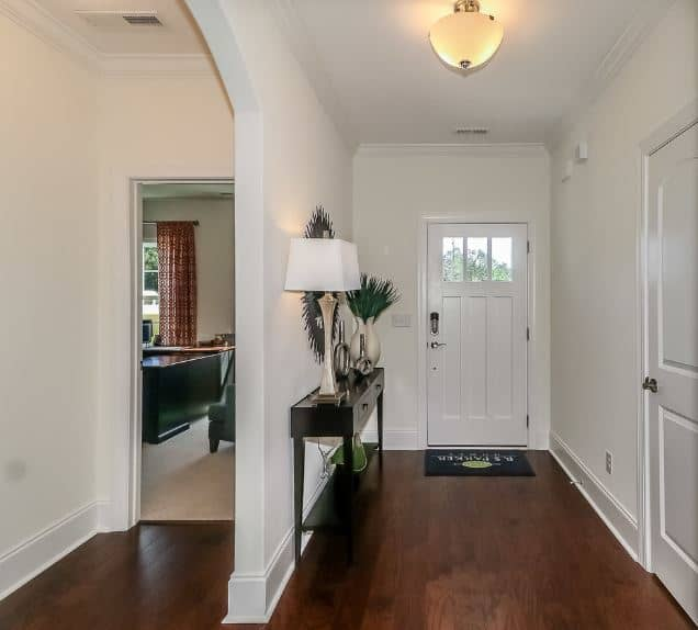 This intimate foyer has a dark hardwood flooring blending with the dark wooden console table that has drawers and topped with decors standing out against the stark white walls, main door and ceiling that bears a yellow semi flush light.